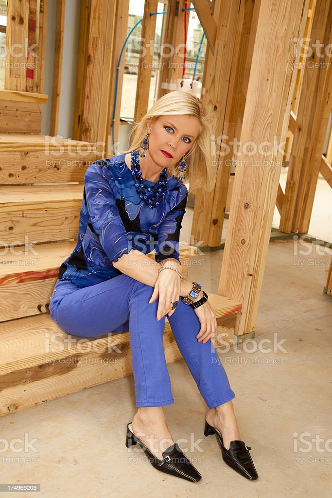 Fashion model in home under construction sitting on stairs royalty-free stock photo