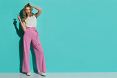 Young woman in red striped wide leg trousers and sneakers is standing with ahnd in hair and looking at camera. Full length studio shot on turquoise background.