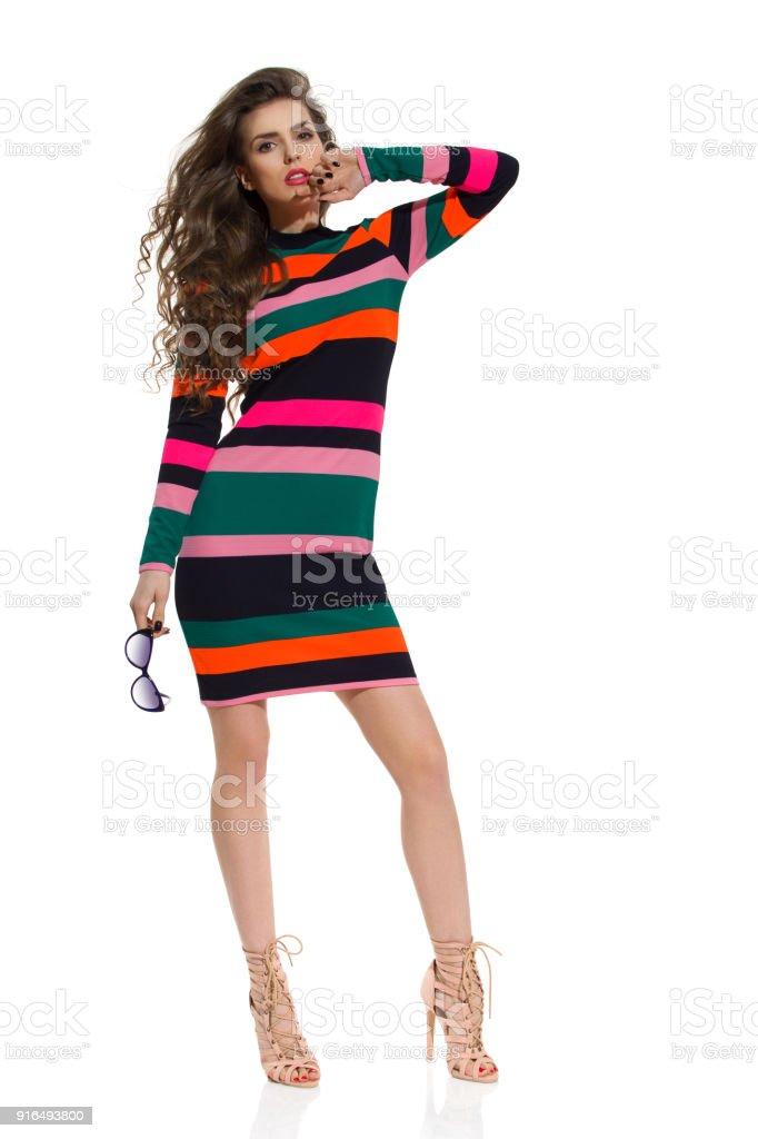 Mannequin en robe Mini rayée et hauts talons pose avec lunettes de soleil  photo libre de ffe5b4171752