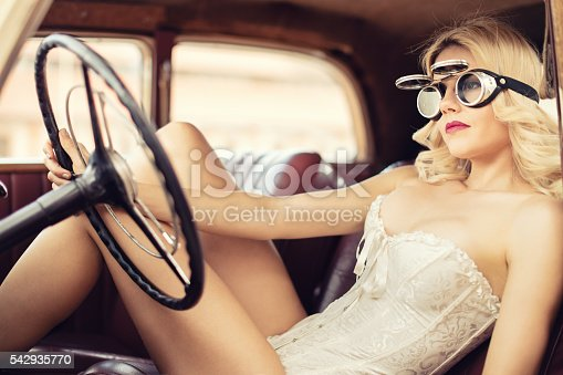 Fashion model in beige corset sitting on front seat in vintage car and she has fashionable eyeglasses. She is very attractive, has a long blond hair and beautiful face. Car has a red leather seats. Photo post processed in retro style.