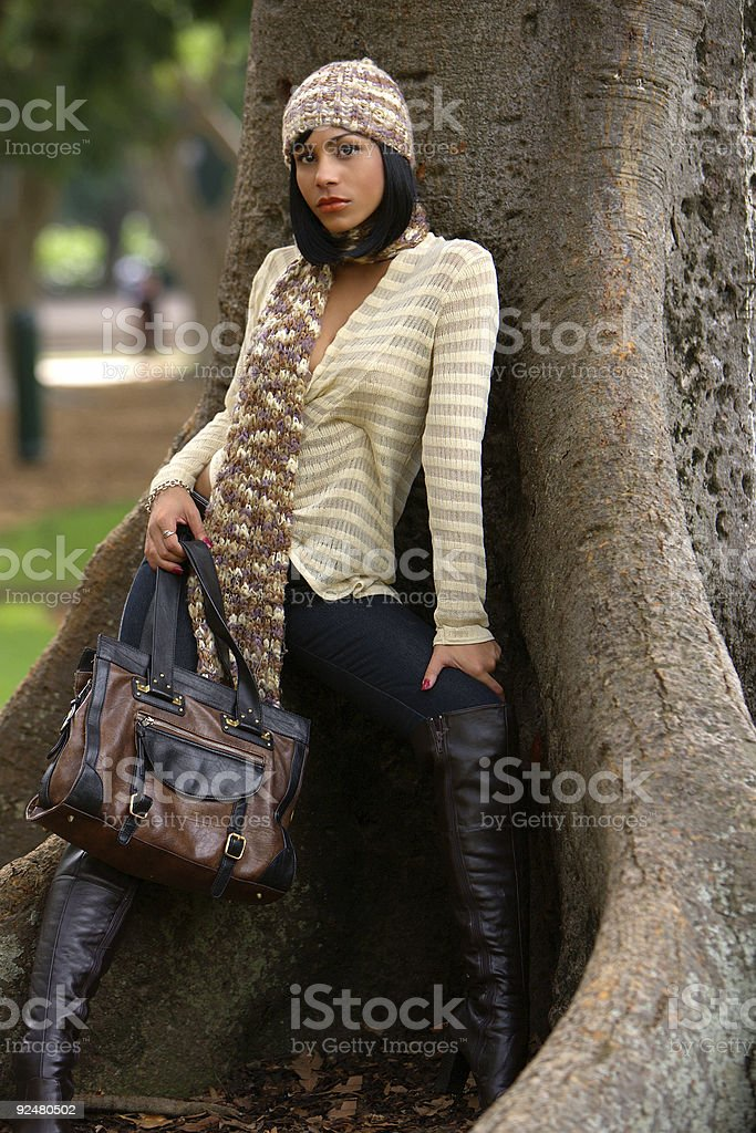 Fashion model in winter clothing in a park by a tree royalty-free stock photo