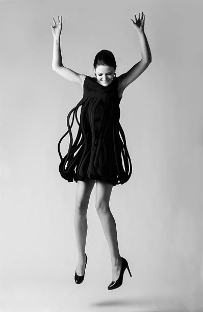 Fashion model jumping in a vintage Avant- Garde dress stock photo