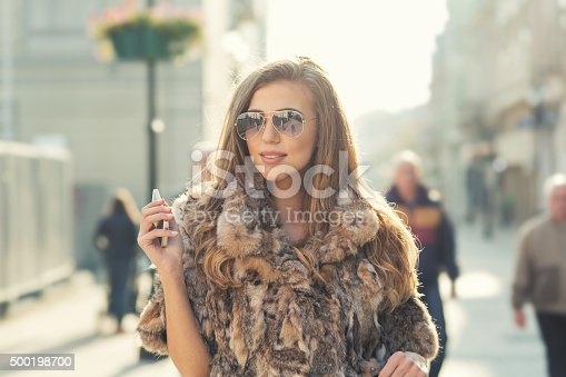 Young fashion model girl walking on the street and holding smart phone in her right hand . Shallow depth of field.