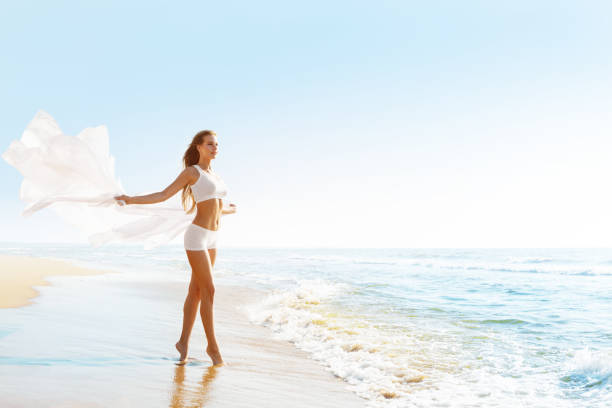 Fashion Model on Sunny Sea Beach, Woman in White Sexy Clothing, Cloth Fluttering on Wind stock photo