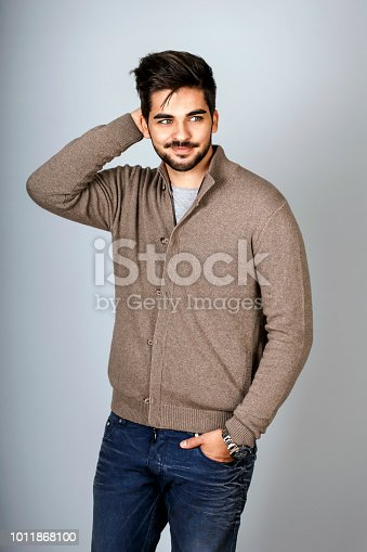 Fashion model posing on gray background. About 25 years old, Caucasian male with beard.