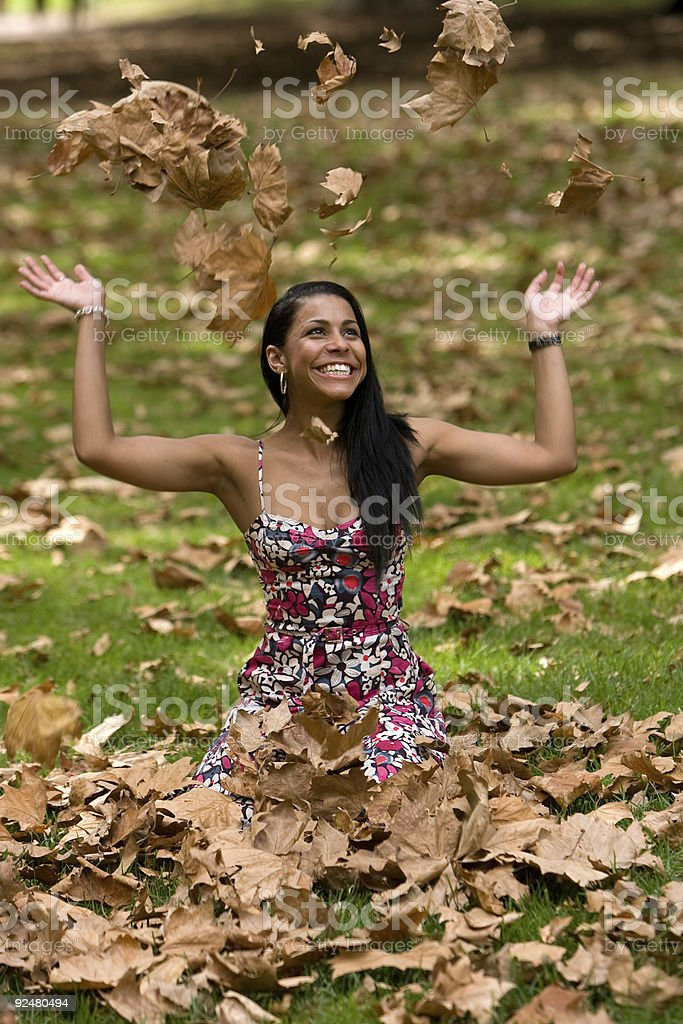 Fashion model playing in Autumn leaves royalty-free stock photo