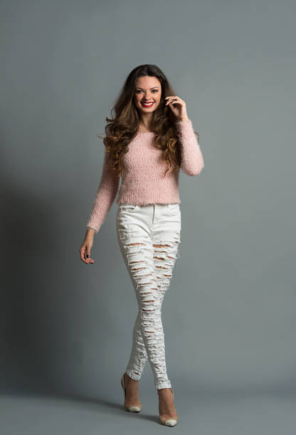 Fashion model posing in studio Fashion model posing in studio skinny jeans stock pictures, royalty-free photos & images