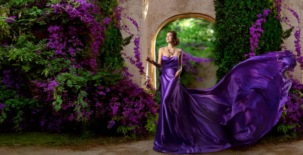 fashion model purple dress, woman long silk gown, violet garden flowers, flying fabric - prom fashion stock photos and pictures