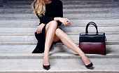 istock Fashion model sitting in black dress with big bag high heel shoes 947152184