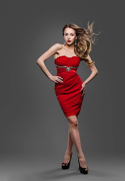 fashion model waving hair, young woman posing in red dress - enge kleider stock-fotos und bilder