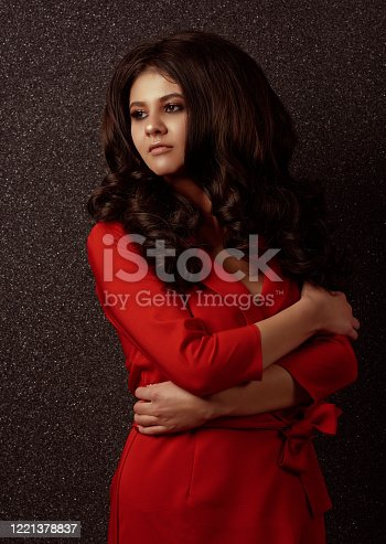 Brunette fashion model posing in a red dress with her arms crossed, looking away seriously