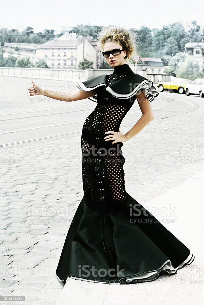 Fashion Model Wearing Haute Couture Gown and Hitchhiking royalty-free stock photo