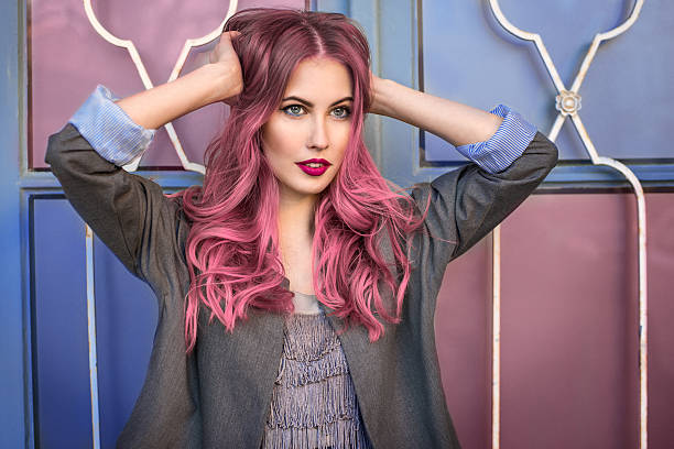 fashion model with curly pink hair posing near colorful wall - beautiful curvy girls stock photos and pictures
