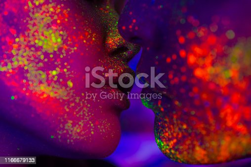 Portrait of fashionable couple  with colored fluo painting on the face - Fashion models on colored background