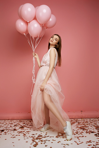 579443552 istock photo fashion model woman in dress holding pastel pink air balloons 1217603190