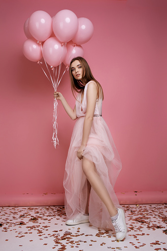 579443552 istock photo fashion model woman in dress holding pastel pink air balloons 1217603235