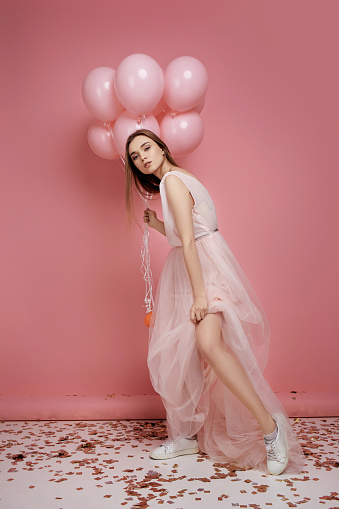 579443552 istock photo fashion model woman in dress holding pastel pink air balloons 1217603359