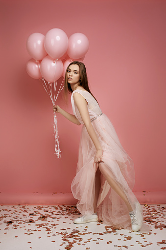 579443552 istock photo fashion model woman in dress holding pastel pink air balloons 1217603362