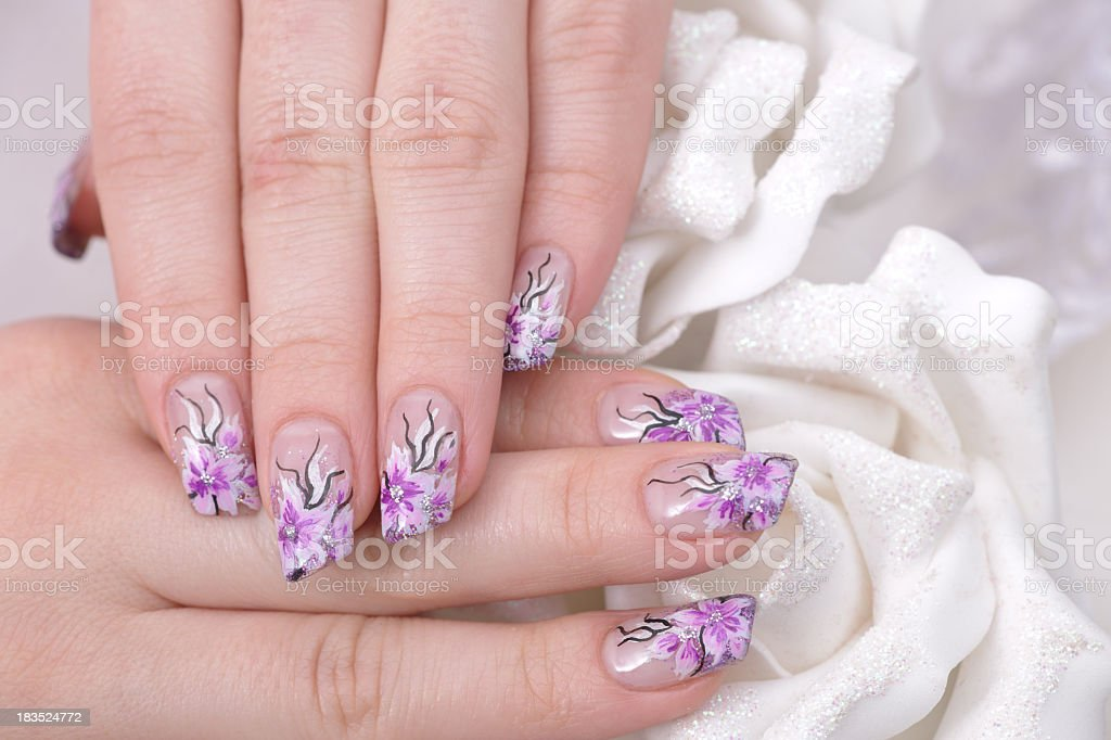 beautiful woman hand having artificial nails with pink, white and...