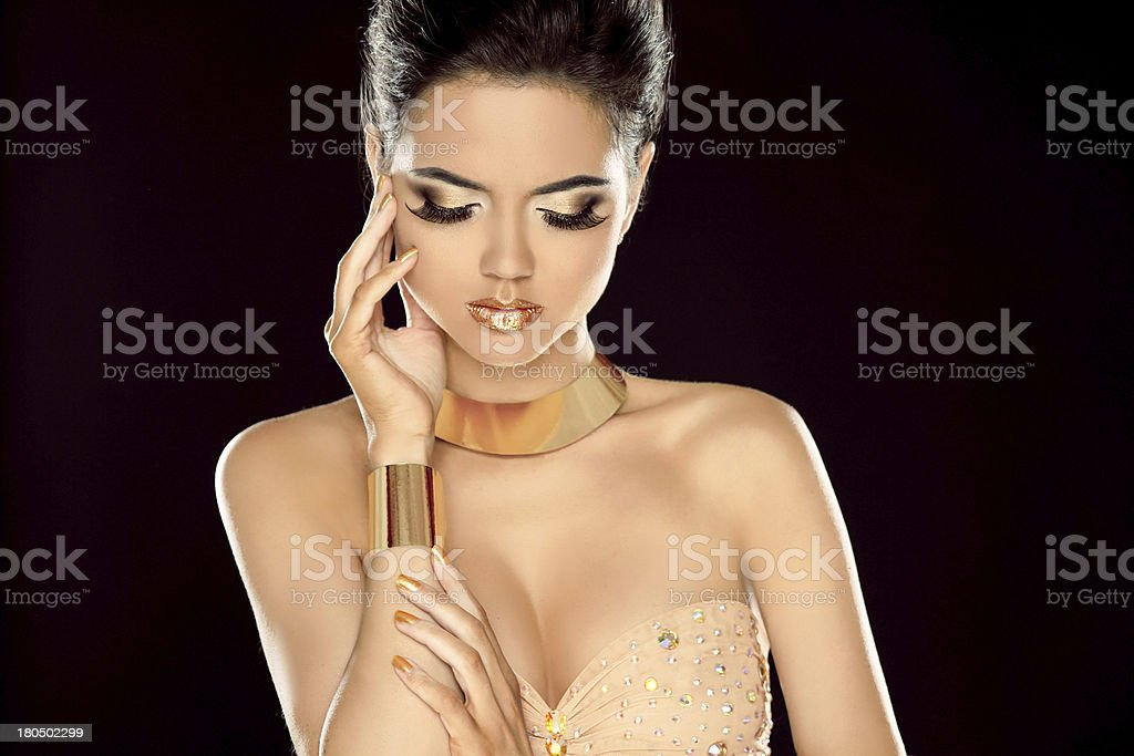 Fashion photo of beautiful brunette woman posing in golden royalty-free stock photo