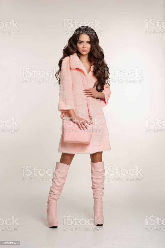 Fashion photo of fashionable woman in pink coat with handbag wears in trendy leather high boots posing isolated on studio background. stock photo