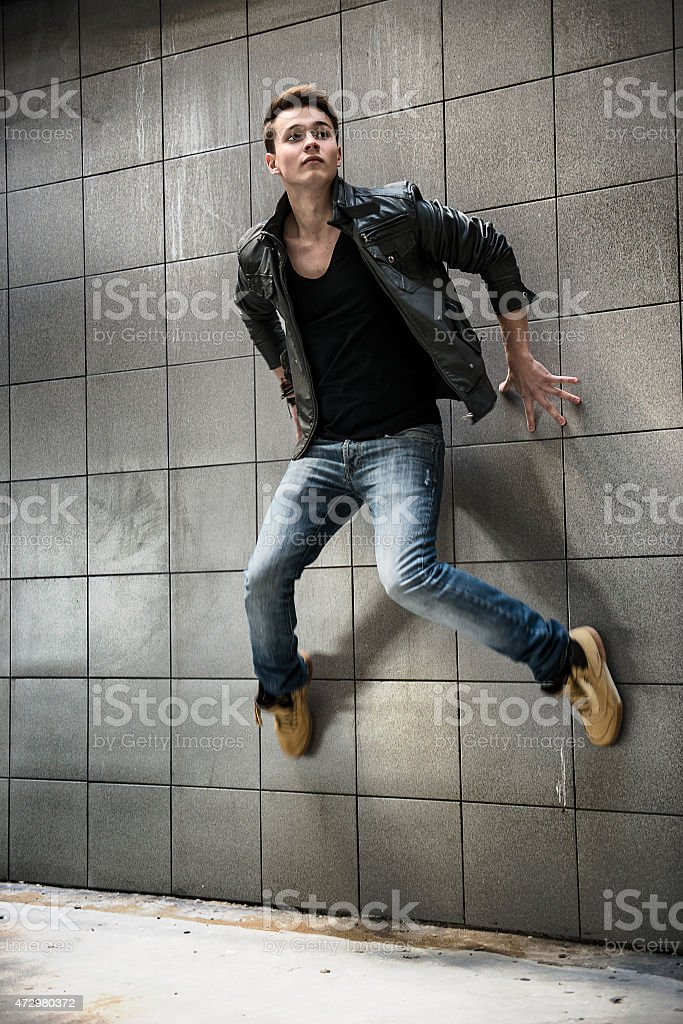 fashion photo of handsome man jumping on the street wall stock photo