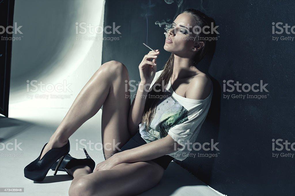 Fashion photo of sexy woman smoking a cigarette stock photo