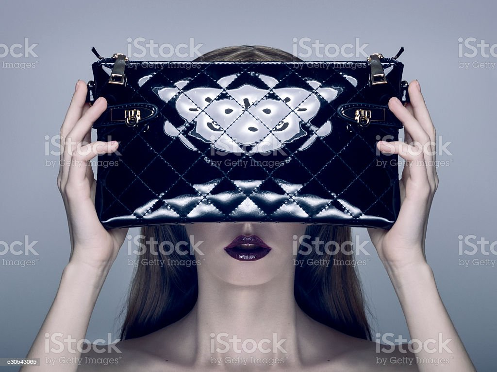 Fashion Photo of Young Pretty Blonde Woman holding a Handbag stock photo