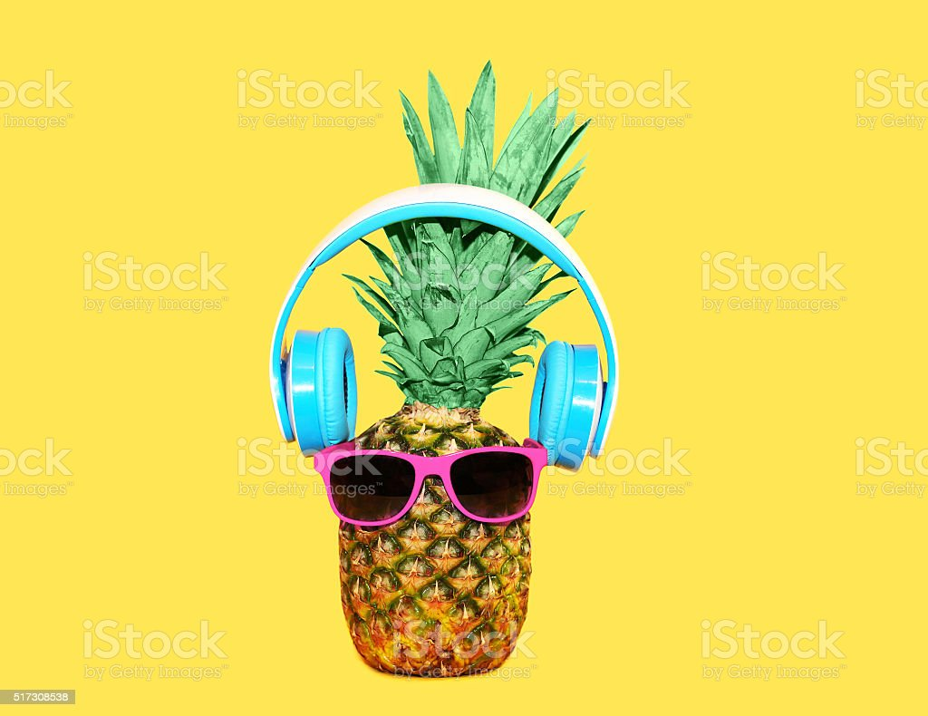 Fashion pineapple with sunglasses and headphones listens music stock photo