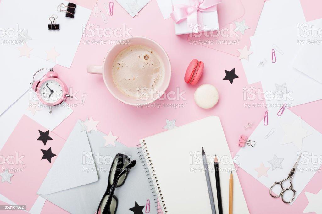 ファッション ピンク女性職場の背景。コーヒー、マカロン、事務用品、ギフト、ブログのきれいなノート。 ストックフォト