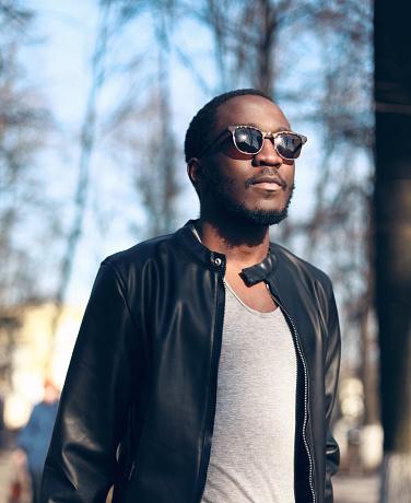 627398448 istock photo Fashion portrait african man wearing sunglasses, black rock jacket 636345422