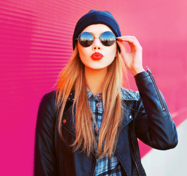 Fashion portrait beautiful blonde woman sending sweet air kiss in rock black style jacket, hat on city street over colorful pink wall background stock photo