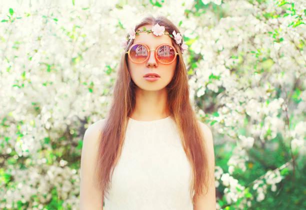 fashion portrait schöne hippie-junge frau über blühende weiße garten hintergrund - hippie stirnbänder stock-fotos und bilder