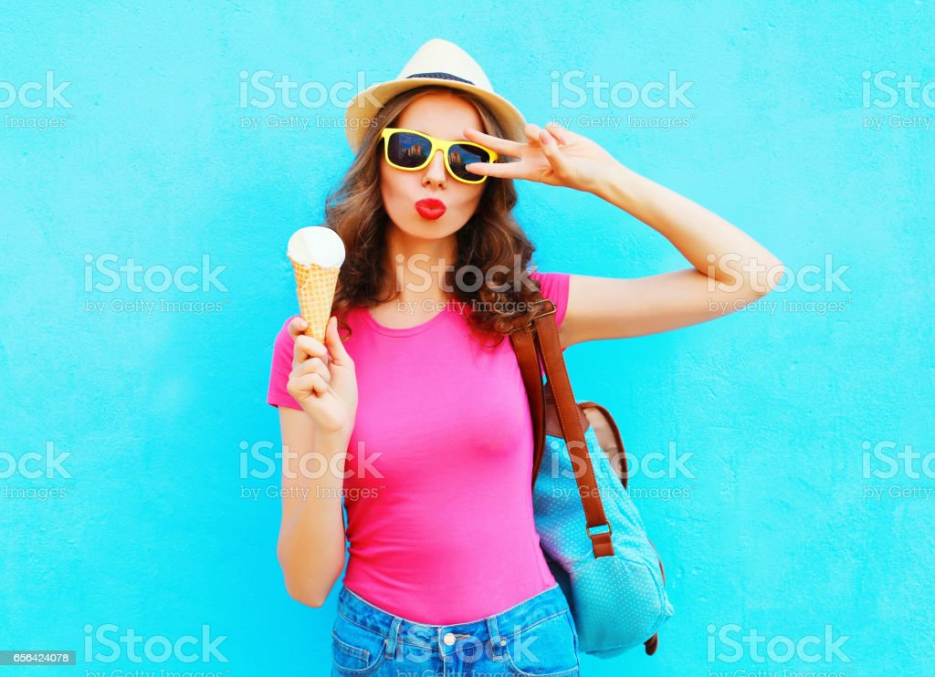 Fashion portrait cool young woman with ice cream over colorful blue background stock photo