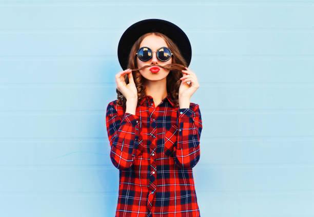 mode porträt lustige junge frau zeigt schnurrbart haar weht rote lippen, die spaß auf blauem hintergrund - flippige outfits stock-fotos und bilder