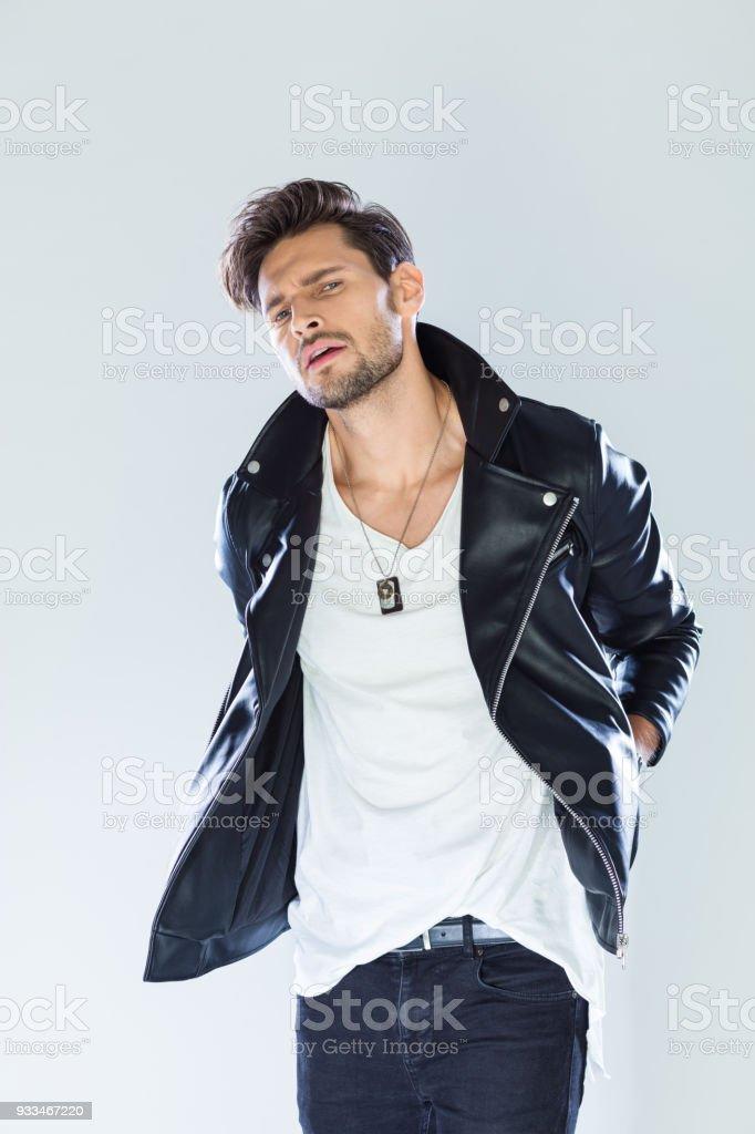 Fashion portrait handsome macho wearing leather jacket Fashion portrait of handsome man wearing black leather jacket, looking at camera. Studio shot, grey background. 25-29 Years Stock Photo