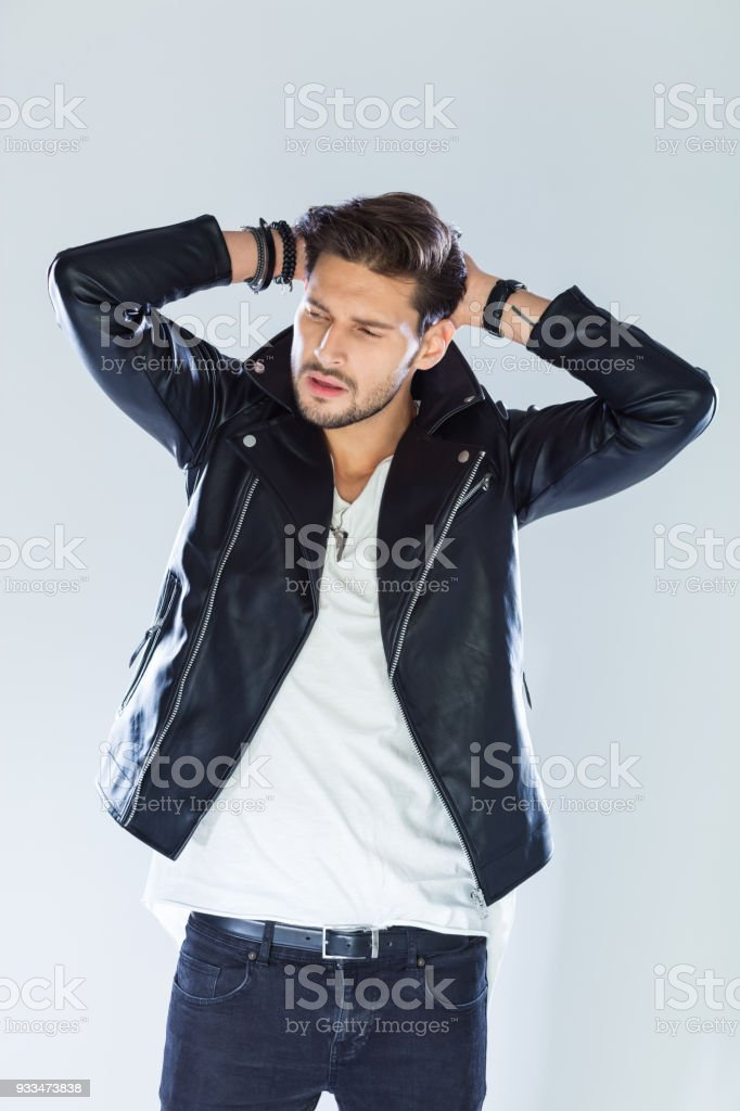Fashion portrait handsome macho wearing leather jacket Fashion portrait of handsome man wearing black leather jacket, raising arms. Studio shot, grey background. 25-29 Years Stock Photo