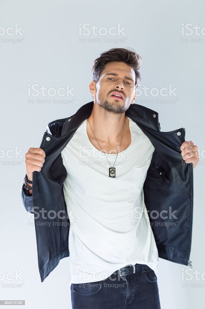 Fashion portrait handsome macho wearing leather jacket Fashion portrait of handsome man wearing black leather jacket, looking at camera. Studio shot, grey background. 25-29 Years Stock Photo