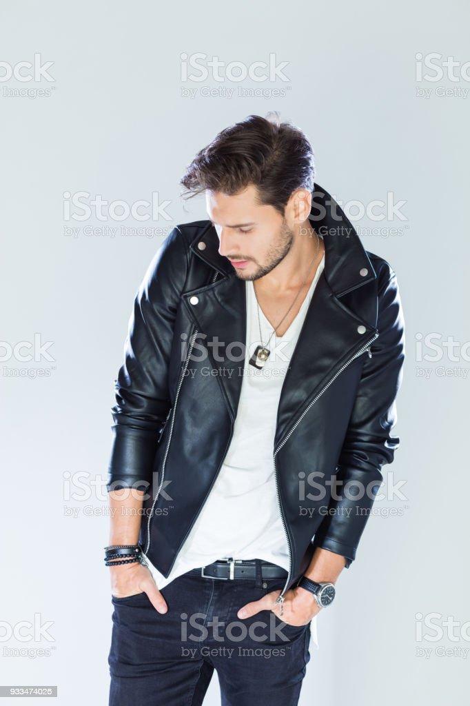 Fashion portrait handsome man wearing leather jacket Fashion portrait of handsome man wearing black leather jacket. Studio shot, grey background. 25-29 Years Stock Photo