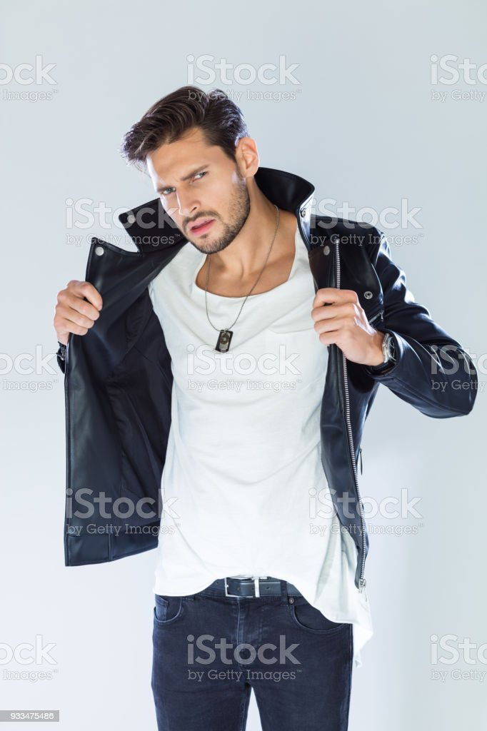 Fashion portrait handsome man wearing leather jacket Fashion portrait of handsome man wearing black leather jacket, looking at camera. Studio shot, grey background. 25-29 Years Stock Photo