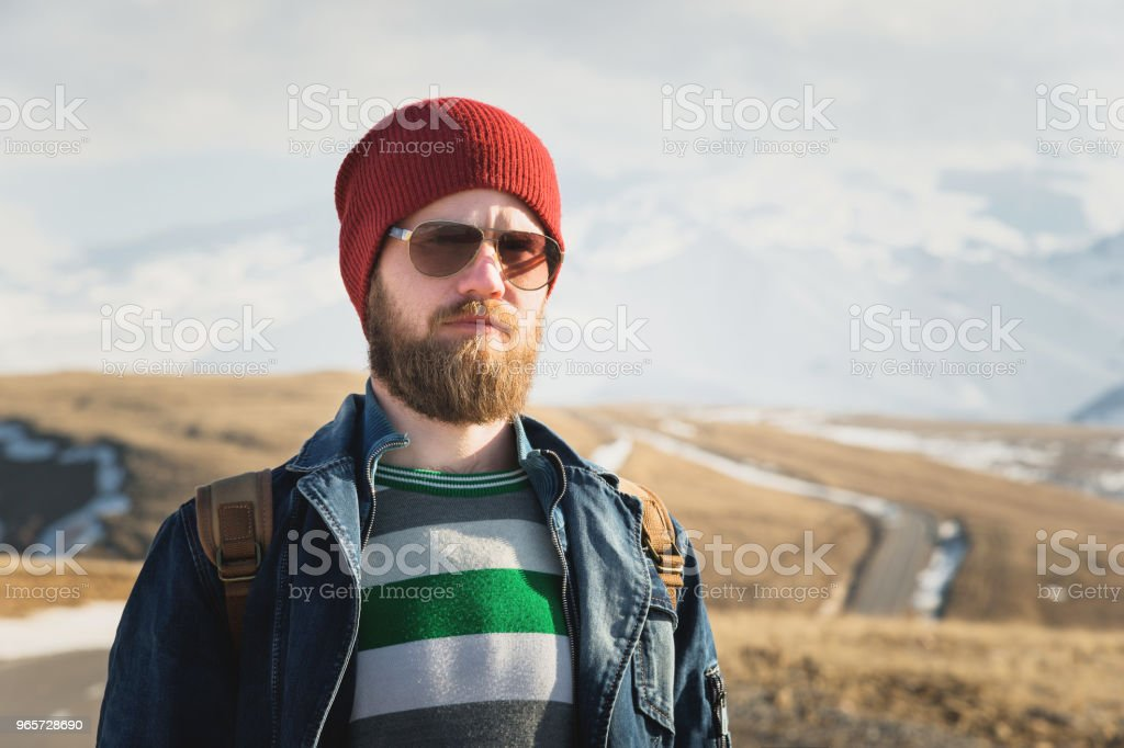 Fashion portrait of a bearded hipster young man wearing sunglasses, a backpack and hat on a background with copyspase in the mountains at sunset .. A confident man with a beard - Royalty-free Adult Stock Photo