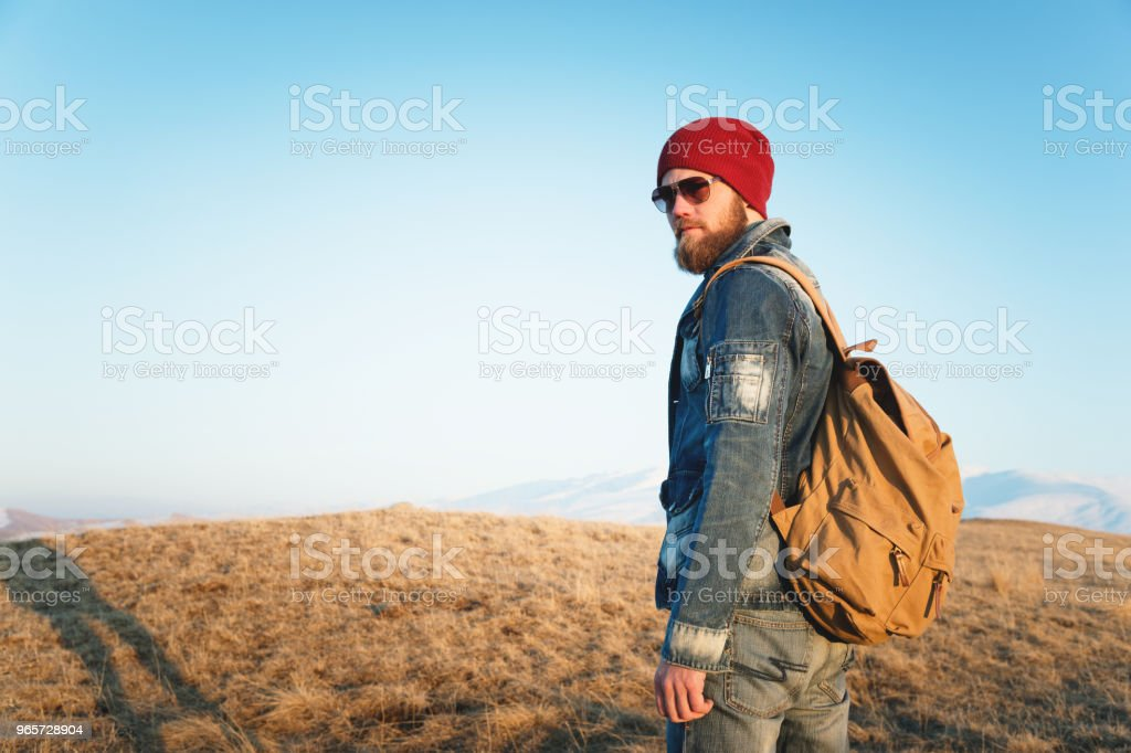 Fashion portrait of a bearded hipster young man wearing sunglasses, a backpack and hat on a background with copyspase in the mountains at sunset .. A confident man with a beard - Стоковые фото Борода роялти-фри