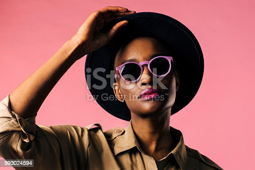 istock A fashion portrait of a young woman with purple sunglasses and black hat 993024594