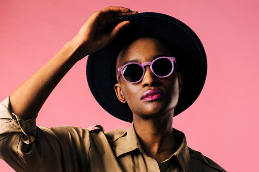 A fashion portrait of a young woman with purple sunglasses and black hat