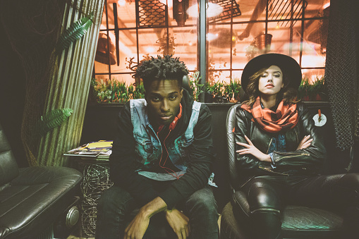 Fashion portrait of contemporary afro american guy and beautiful woman sitting in cool pub and looking at camera.