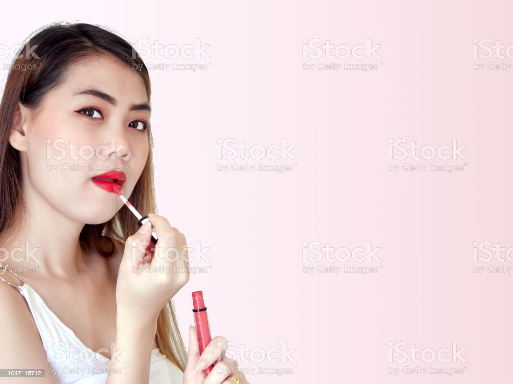 Fashion portrait of Asian woman with color bright red lips,makeup with applying lipstick to her mouth,The girl in her hand holds a lip gloss,on studio ...