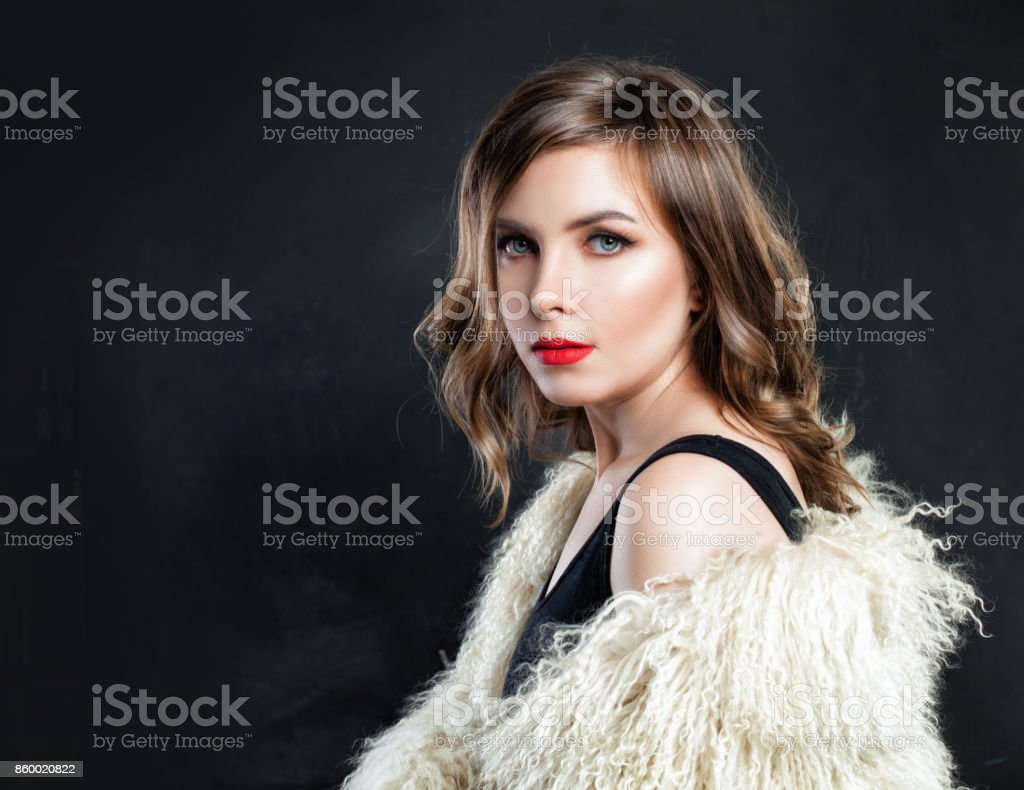 Fashion Portrait of Beautiful Fashion Model in Autumn or Winter Clothes. Cute Woman Wearing Stylish Fur Coat and Evening Dress stock photo