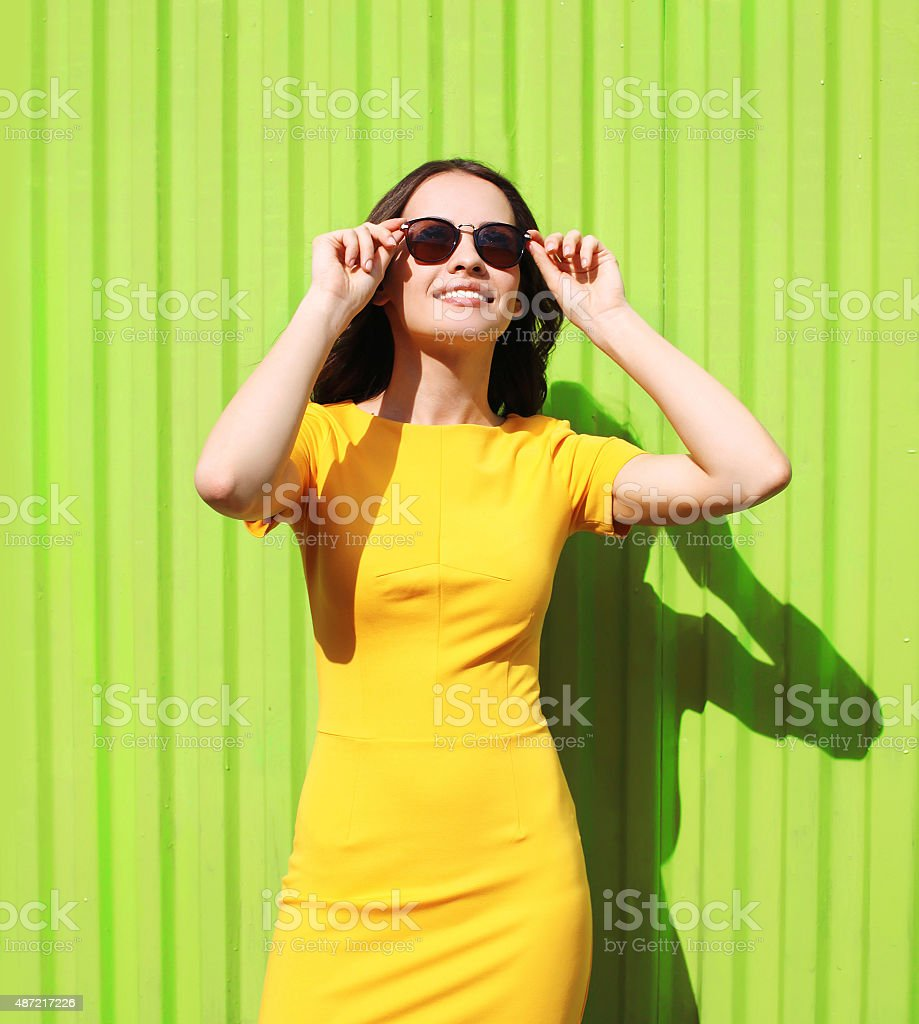 Fashion portrait of beautiful smiling young woman in yellow dres stock photo