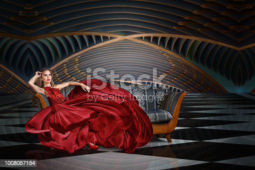 Fashion portrait of beautiful woman in long dress sitting on sofa