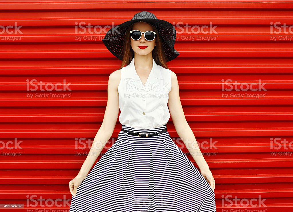 Fashion portrait of beautiful woman wearing a black straw hat stock photo